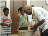 Wilton Dubois demonstrating drums to children