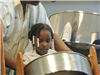 Young girl playing tin drum