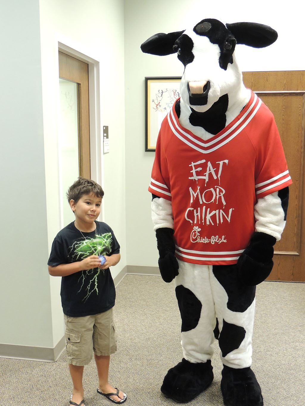 Cow posing with boy