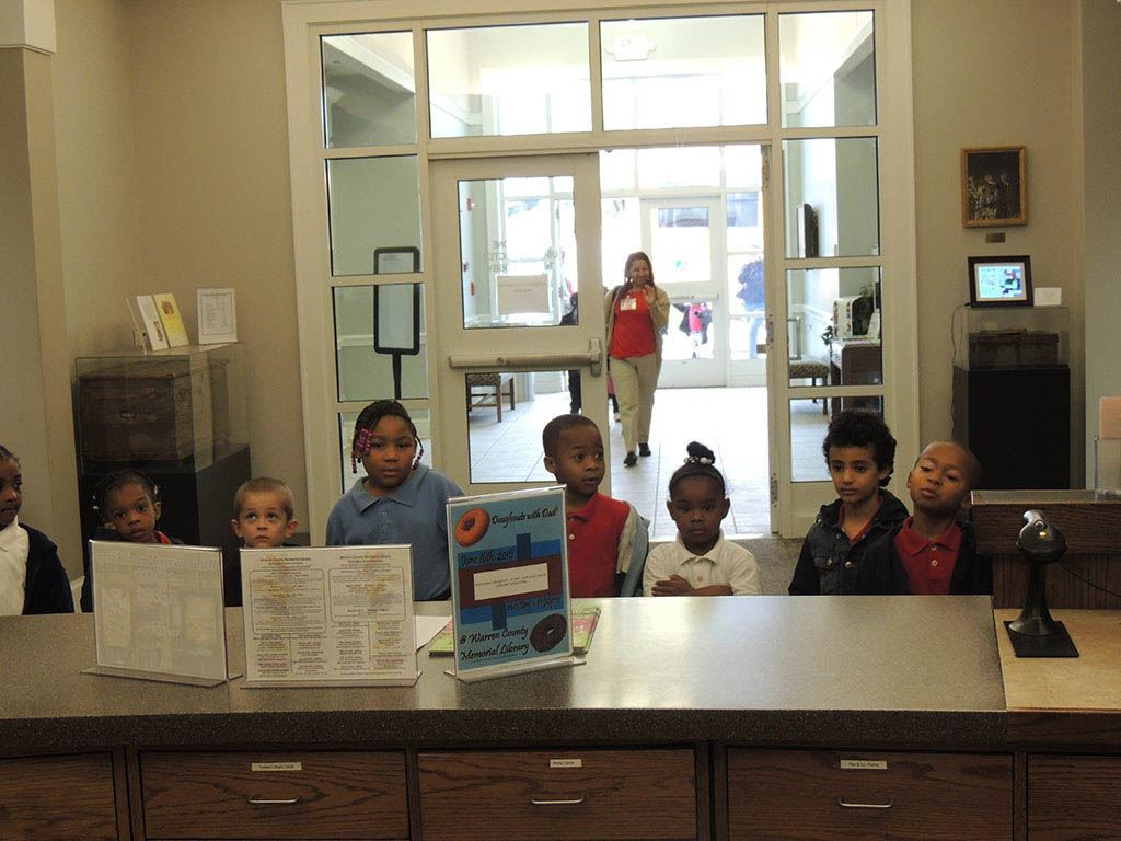 Children standing in front of desk