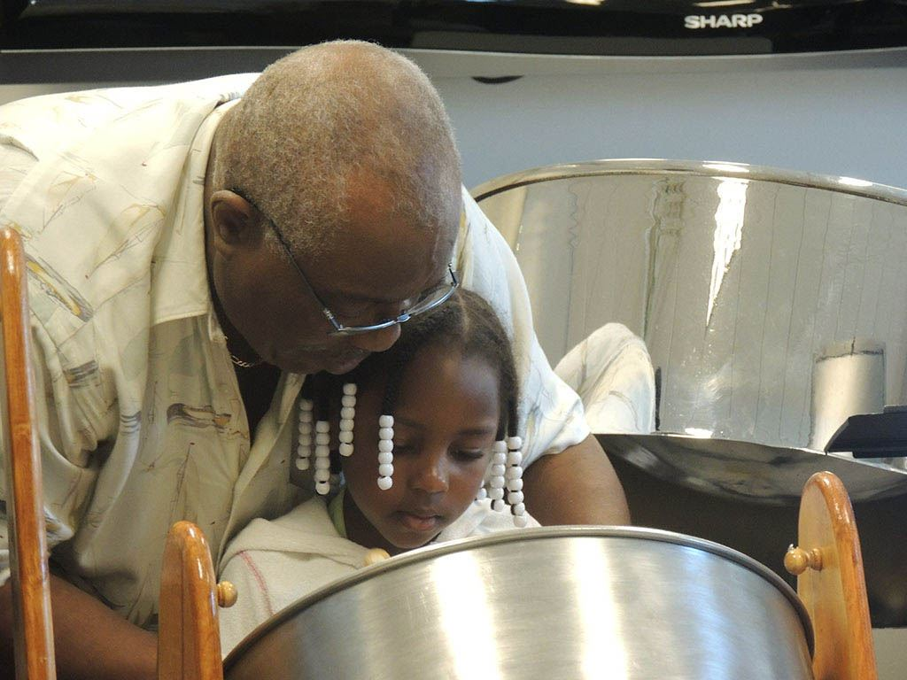 Wilton Dubois helping girl play drum