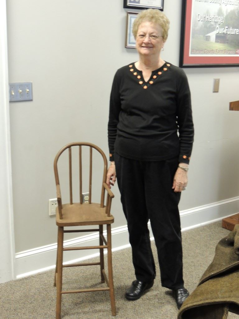 Woman standing by chair