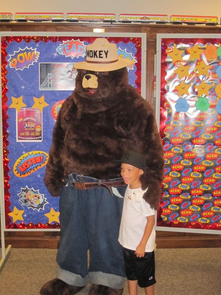 Smokey the Bear standing with boy