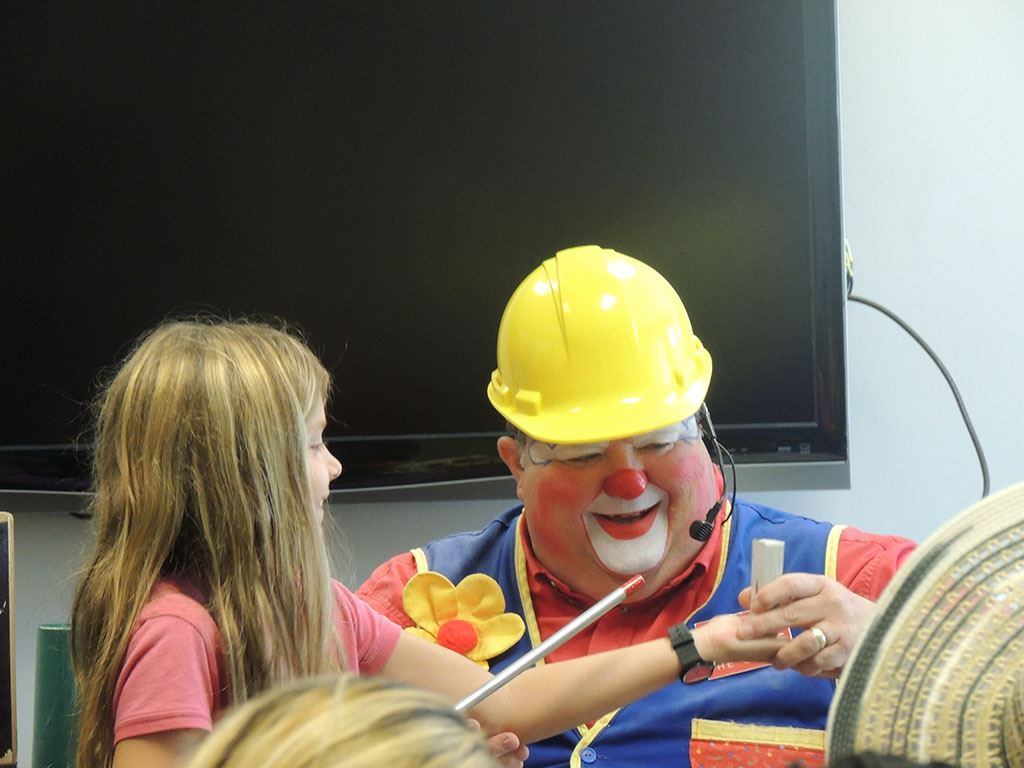 Clown doing card trick with young girl