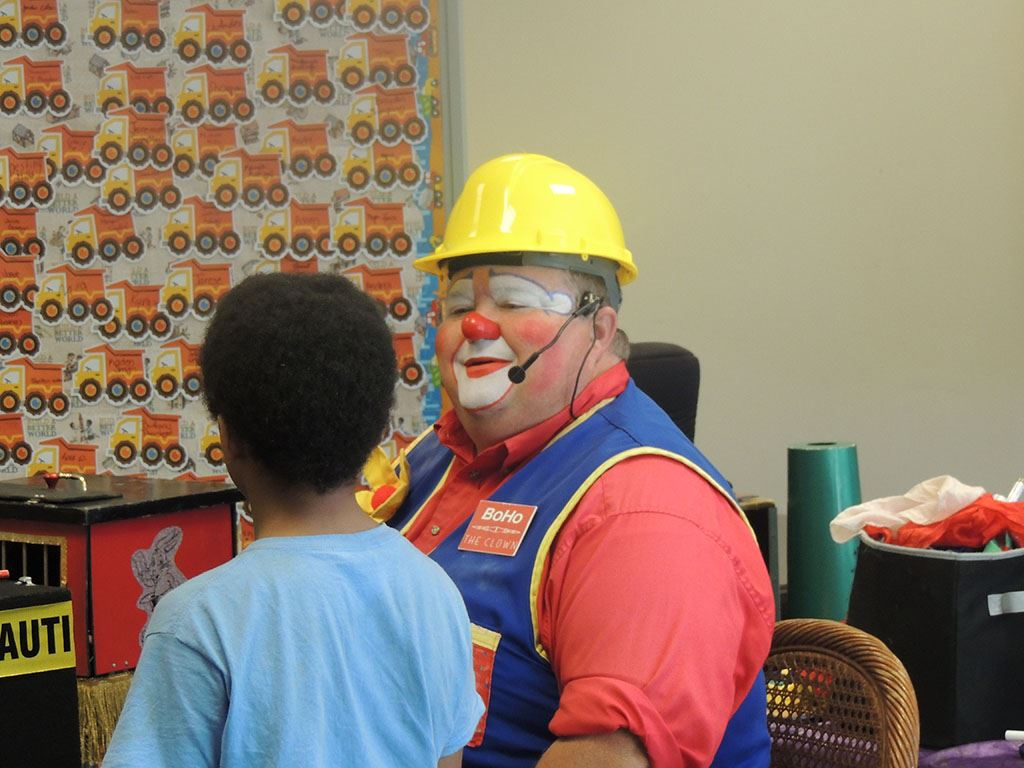 Clown with hard hat on talking to child