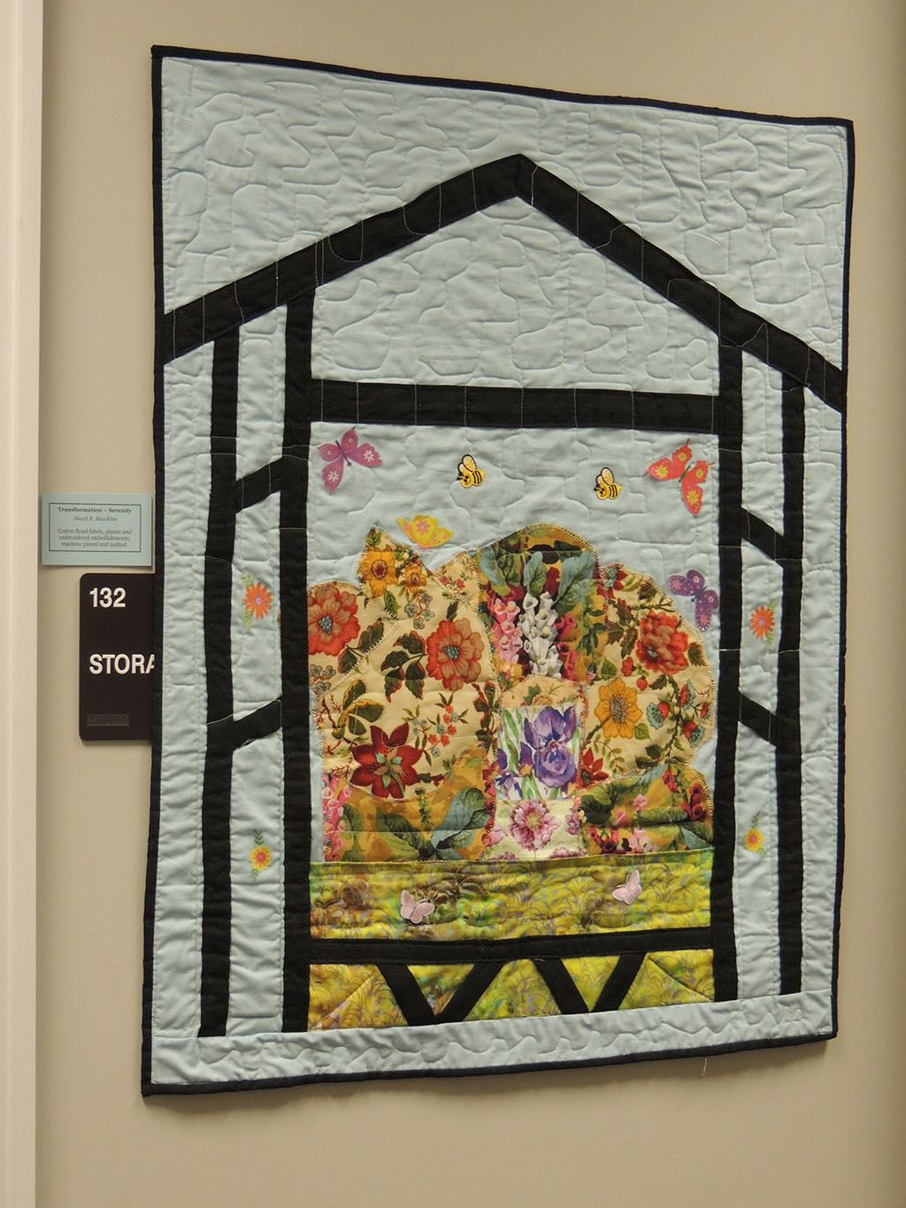 Quilt artwork on house filled with flowers