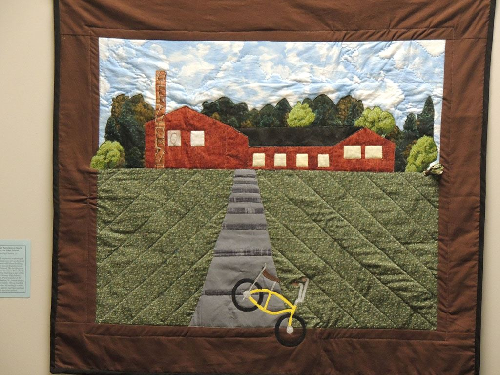 Quilt showing bike in front of building