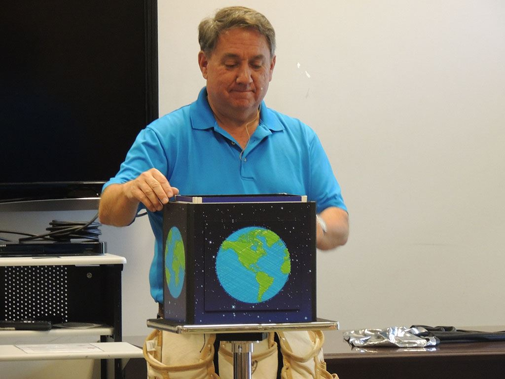 Presenter holding box with earth painted on it