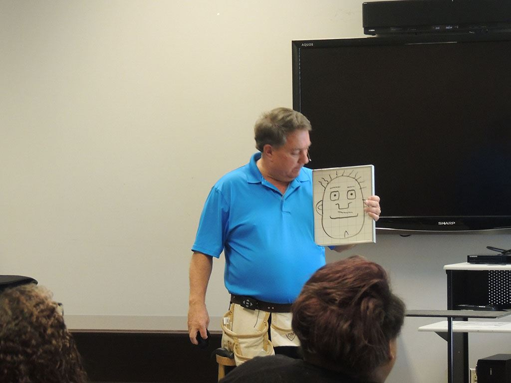 Presenter holding drawing of a face