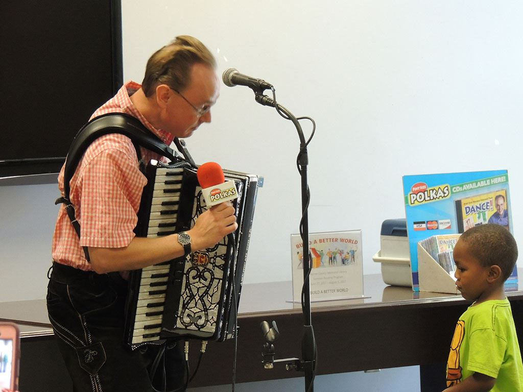 Polka Man holding mic talking to young boy