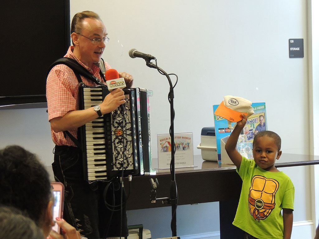 Polka man playing accordion with child helper