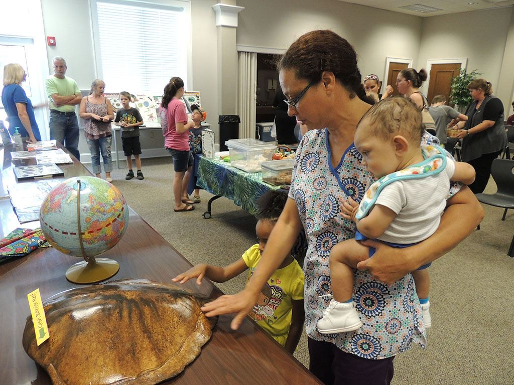 Woman and baby looking at display objects