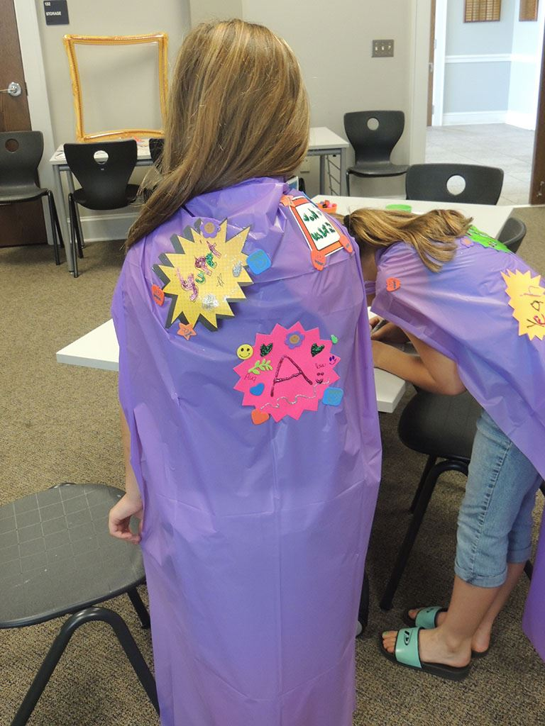 Girl wearing purple cape she made