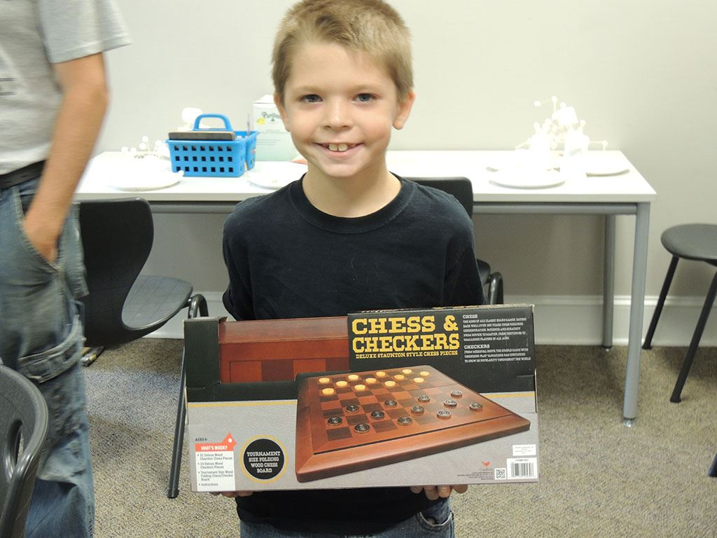 Boy holding chess and checkers board game