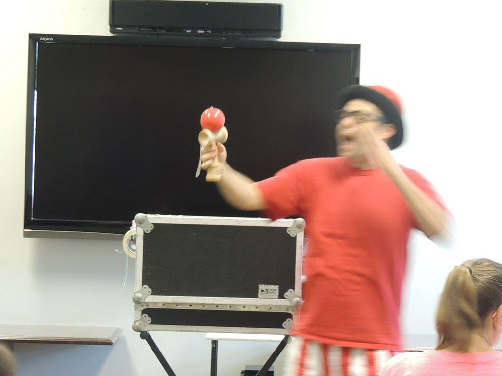 Presenter holding red ball toy