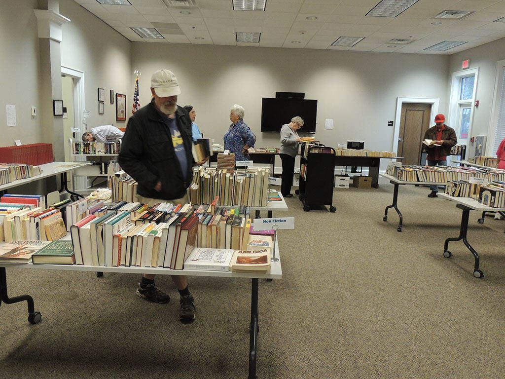 People looking through books on tables