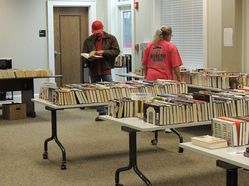 People looking through tables of books