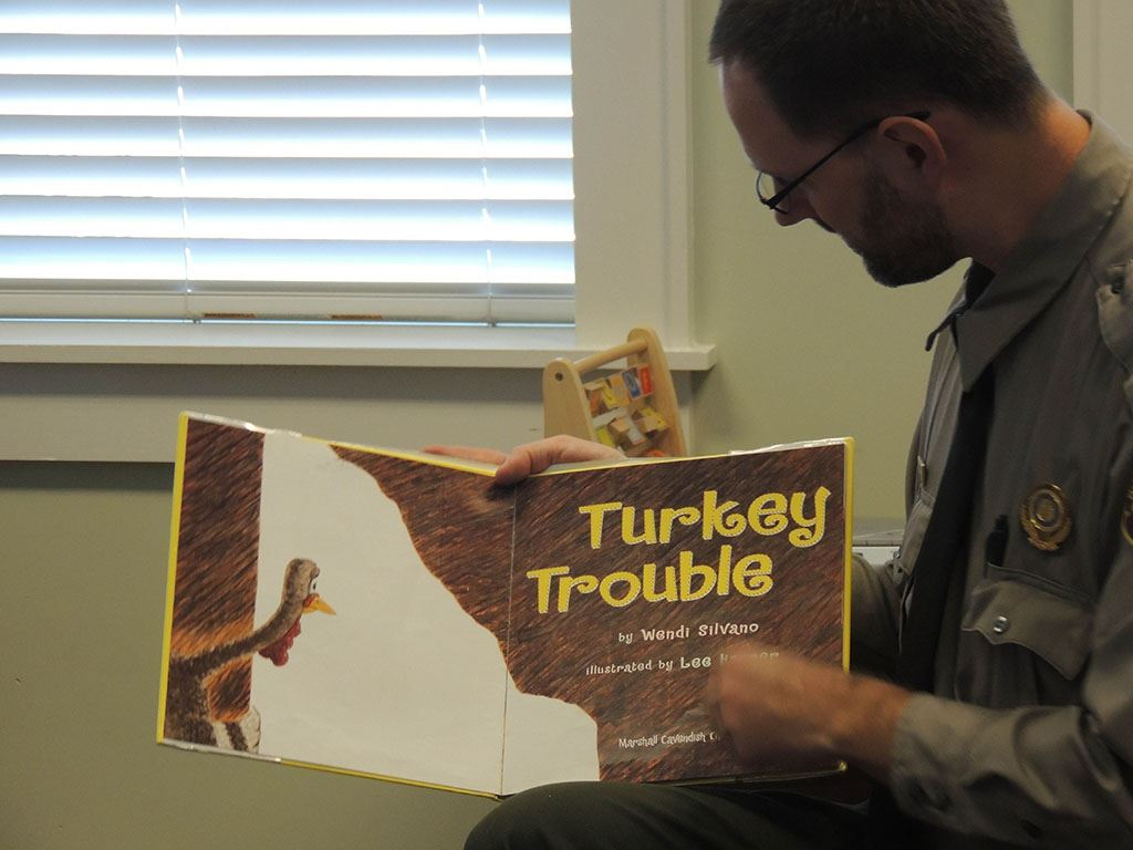 Man holding book titled Turkey Trouble