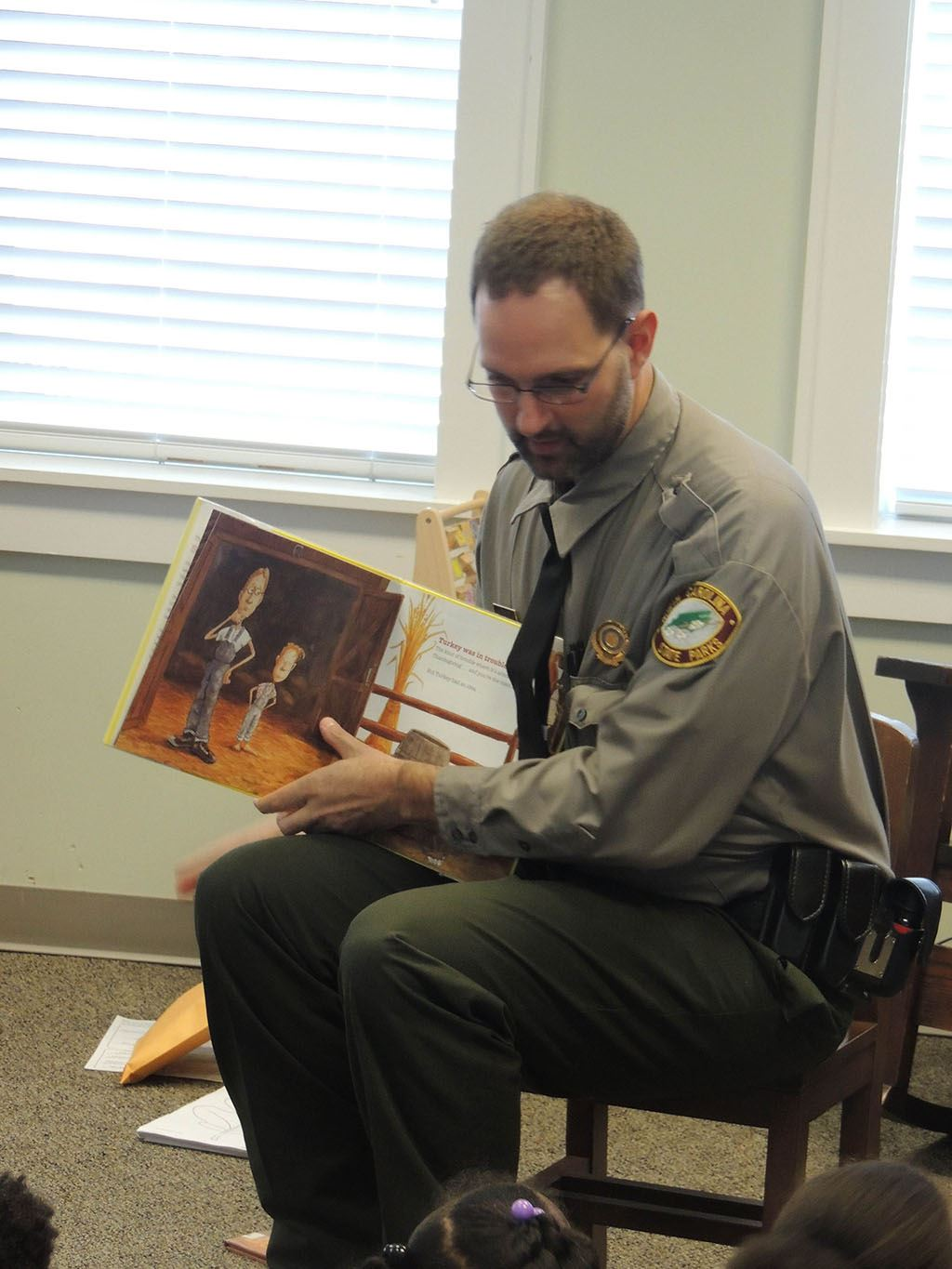 Uniformed man holding picture book