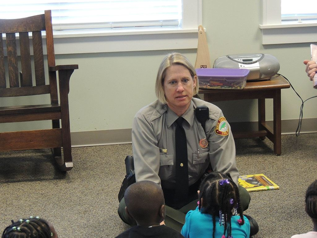 Uniformed woman talking to children