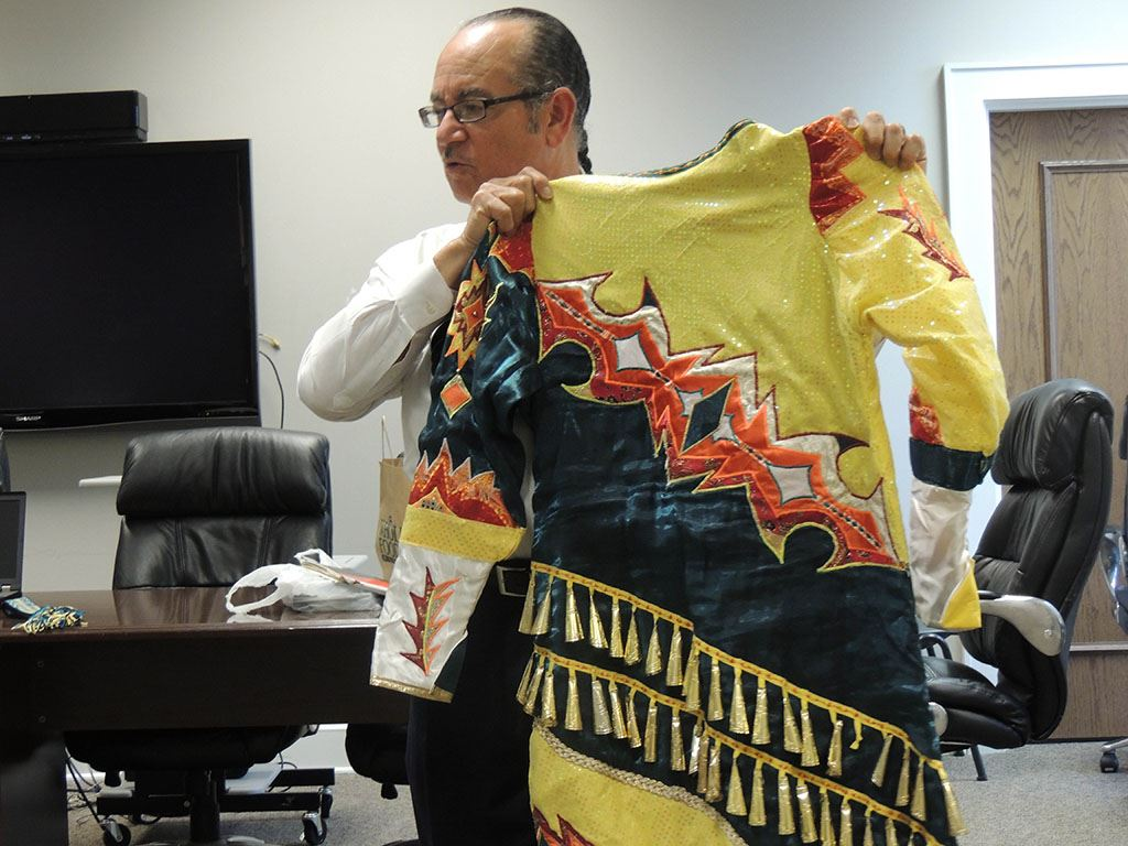 Man holding Native American garment